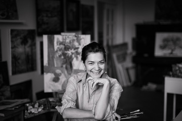 Portrait of a young smiling brunette woman artist in her studio. Black and white picture.