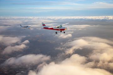 Fototapeta Popular single-engine airplane flying through the clouds on a beautiful sunset sky obraz