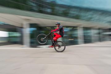 Bike-Artist übt auf Hinterrad in der Fußgängerzone