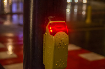Hand pushing control button on pedestrian crossing to activate the green traffic light; in the dark