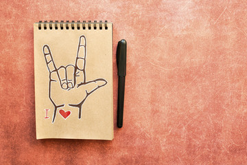 Notebook of Kraft paper, with a painted ASL (American sign language) symbol I Love you (ILY). Suitable for congratulations to the holiday Valentines day