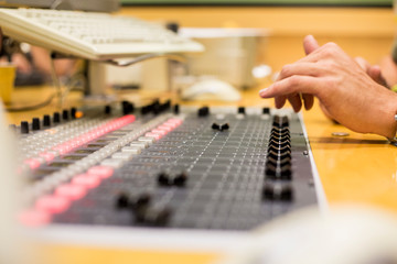 sound technician manipulating mixer in a radio station