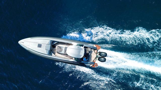 Aerial top view luxury inflatable rib speed boat cruising in mediterranean deep blue sea