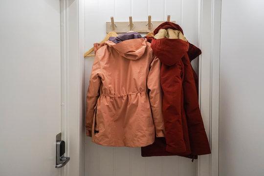 men and women winter jacket hang at wall hook at house door