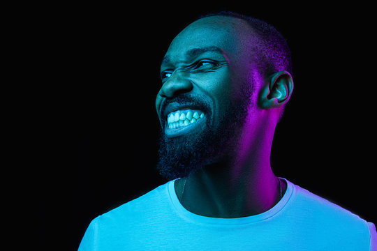 The retro wave or synth wave portrait of a young happy smiling african man at studio. High Fashion male model in colorful bright neon lights posing on black background. Art design concept
