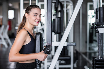 Cinematic tone of young attractive fitness woman exercise with machine in gym. Healthy, workout and diet life style concept.