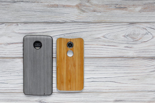 mobile phone with wooden back cover.Stylish protective cover on the phone.two phones on a wooden background. background for phone shop
