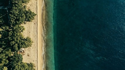 stunning aerial drone minimal geometric image of a remote tropical sea ocean shore with sandy beach lush rainforest jungle and crystal clear azure blue water from top looking down at sunset