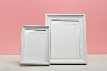 white frames on white desk near pink wall