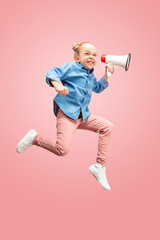 Beautiful young child teen girl jumping with megaphone isolated over pink background. Runnin girl in motion or movement. Human emotions,, facial expressions and advertising concept