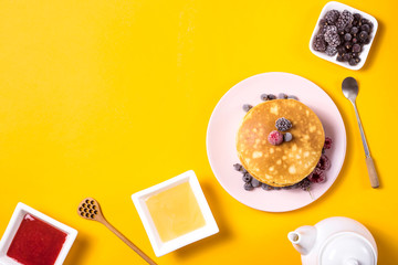 A stack of pancakes on a pink plate with berries next to a plate of honey and jam with wooden spoons on a bright yellow background. Top view, copy space