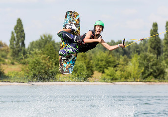 Wakeboarder im Flug zeigt Daumen hoch