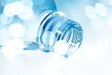Water Drop Pouring out of Plastic Bottle on the Blue Background