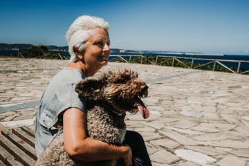 White hair middle-aged woman sitting in the company of her friendly dog ​​on a wooden bench overlooking the sea on a sunny and breezy summer morning. Lifestyle.