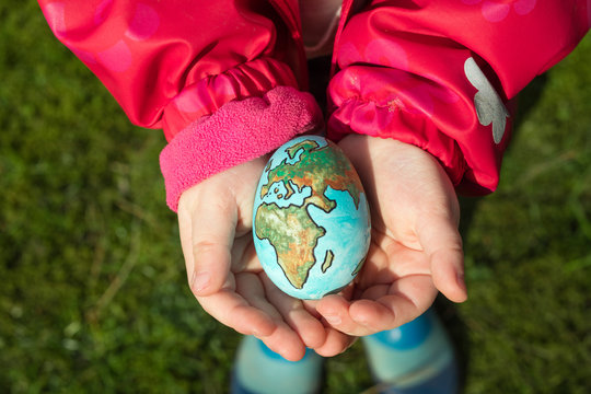 Child holding an egg with Planet Earth painted on it on a sunny day outdoors
