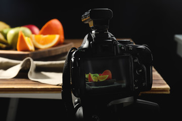 Tasty fruits on display of professional photo camera in studio