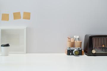 Mockup Blank poster, books, vintage radio and vintage camera on workspace desk