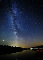 Milky way and stars over the forest and river.