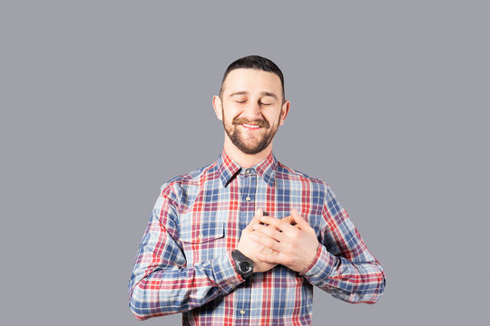 Body language concept. Young handsome man with facial hair posing over gray wall showing emotions. Portrait of masculine bearded male, wearing slim fit checkered shirt. Isolated background, copy space