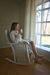Young woman sitting in a rocker chair drinking coffee