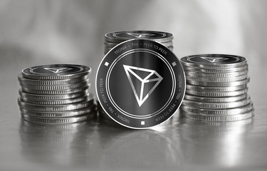Tronix (TRX) digital crypto currency. Stack of black and silver coins. Cyber money.