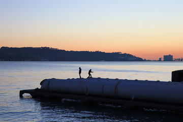 silhouette from two boys running on pipes in a pier at the sunset. Lisbon Portugal