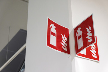 Fire extinguisher sign on the white wall.