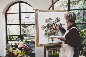 Senior woman wearing glasses, red dress and white apron standing in studio, working on painting of pink tea roses, leaves, berries and other flowers.