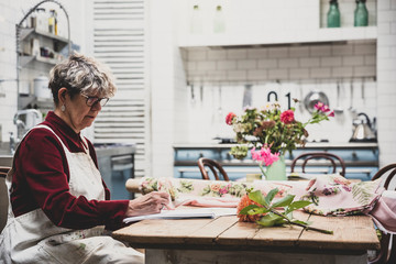 Senior woman wearing glasses, red dress and white apron sitting at table, working on pencil drawing of orange Dahlia.