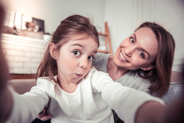 Positive cute girl taking photos with her mom