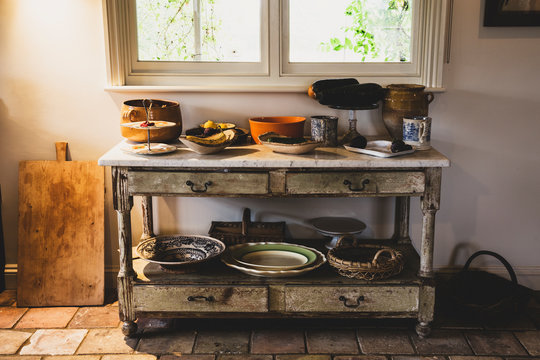 Selection of earthenware bowls and plates on antique court cupboard with drawers.