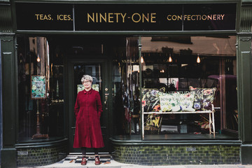 Smiling senior woman wearing glasses and red dress standing front of interior design store, looking at camera.