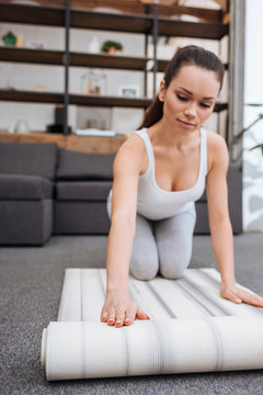 selective focus of woman rolling fitness mat for practicing yoga at home