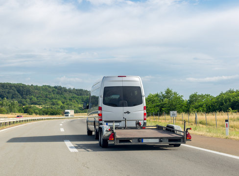 Minibus with empty tow truck transporter on highway. Space for text