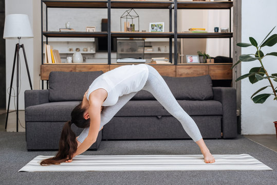 young woman practicing intense side stretch pose at home in living room
