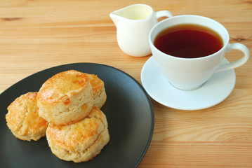 A plate of candied orange peel scones and a cup of hot tea served on wooden table