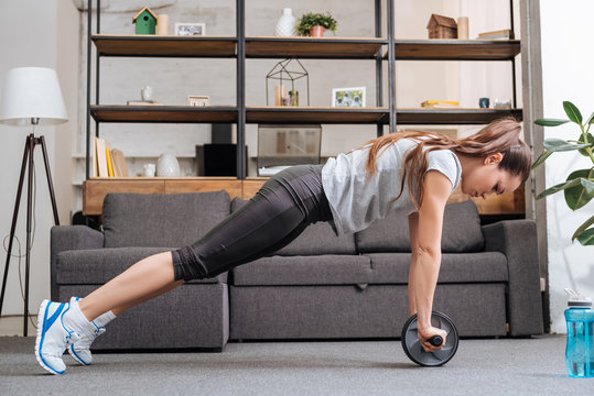 focused sportswoman exercising with ab wheel at home