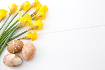 Brown easter eggs and yellow daffodils. Easter background.