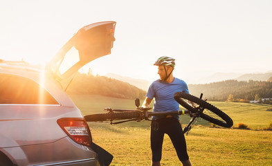 Man put his bicycle in the trunk of a car