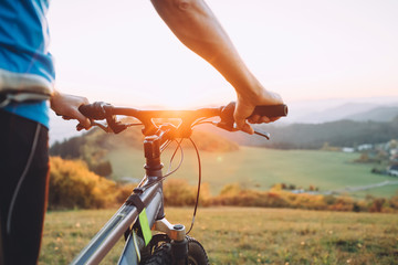 Man with bike stay on the top of hill and enjoying the sunset. Man hands on the bike steering wheel close up image