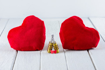 Red Heart shape and Couple Combination golden padlock on white wooden table