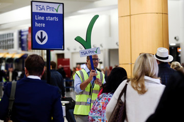 A man guides passengers towards a TSA PreCheck security checkpoint at Hartsfield-Jackson Atlanta International Airport amid the partial federal government shutdown, in Atlanta