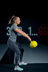 Young woman exercising with kettlebells at the gym. Squats squatting swing WOD fitness gym. Fitness woman workout with kettlebell training at the gym.