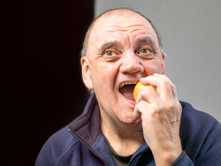 portrait vieil homme croquant dans une pomme