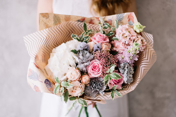 Very nice young woman's hand holding beautiful blossoming bouquet of fresh hydrangea, black molly carnations, roses, eustoma, eucalyptus flowers in white and pink color on the grey wall background