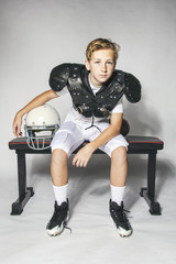 Male Child Football Player in Shoulder Pads Relaxing After Game