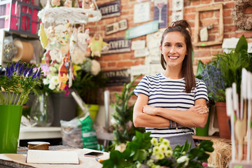 Obraz Picture of young florist standing in her shop and smiling at camera - fototapety do salonu