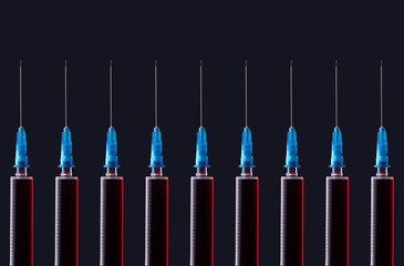 Multiple syringes organized in a pattern over dark background