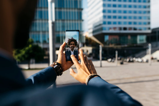 Spain, Barcelona, close-up of young businessman taking a selfie in the city