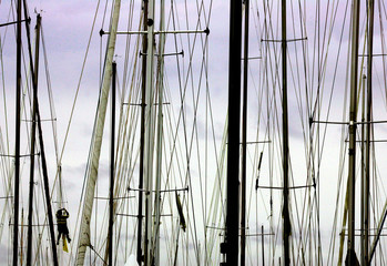 A sailor climbs a mast of a yacht docked with other Sydney-to-Hobart entrants during the official ...